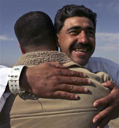 Reuters journalist Ali al-Mashhadani (R), a television cameraman, embraces a colleague shortly after his release from Abu Ghraib prison in Baghdad January 15, 2006. REUTERS/Thaier al-Sudani
