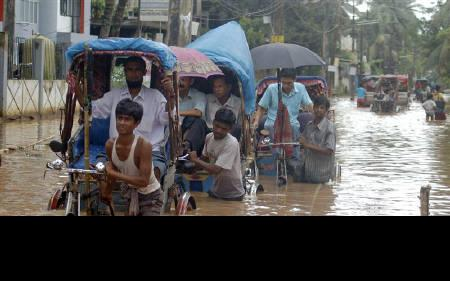 People use rickshaws to cross flooded areas after heavy rain in Guwahati, August 19, 2008. REUTERS/Utpal Baruah/Files