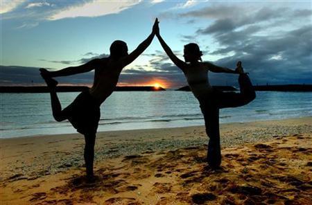Darius Rustam, 30, and Tiffany Davis-Rustam (R) 27, from New York City, practice the King Dancer yoga pose during the sunset hours on Magic Island in Ala Moana Beach Park in Honolulu, Hawaii, January 21, 2004. REUTERS/Lucy Pemoni