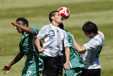 Argentina's Luciano Monzon (C) heads the ball during the men's gold medal soccer match against Nigeria at the Beijing 2008 Olympic Games, August 23, 2008. REUTERS/Gary Hershorn