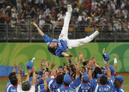 South Korea players throw manager Kim Kyung-moon into the air after defeating Cuba to win the baseball gold medal at the Beijing 2008 Olympic Games August 23, 2008. REUTERS/Jessica Rinaldi
