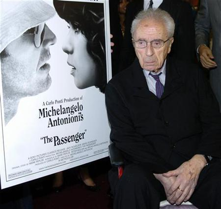 Legendary Italian film director Michelangelo Antonioni poses alongside a poster for his film ''The Passenger'' in Beverly Hills in this undated file photo. REUTERS/Chris Pizzello/Files