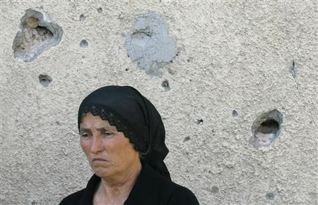 A displaced woman stands in the village of Khetagurovo, during the visit of Council of Europe's Commissioner for Human Rights Thomas Hammarberg, August 24, 2008. A U.S. navy warship delivered humanitarian aid on Sunday for victims of Georgia's brief war with Russia while Moscow ignored Western demands to pull its remaining troops from the Caucasus country's heartland. Russia says residual troops are peacekeepers needed to avert further bloodshed and to protect Georgia's separatist, pro-Moscow provinces of South Ossetia and Abkhazia. Moscow withdrew the bulk of its forces from core Georgia on Friday. REUTERS/Sergei Karpukhin