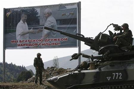 A Russian military vehicle drives in the direction of the Russian border in the South Ossetian settlement of Dzhava, some 25 km from Tskhinvali (15.5 miles), August 22, 2008. The poster reads ''Year of Transdniestria in South Ossetia. We are strong people through brotherly friendship.'' Transdniestria is a breakaway region in the ex-Soviet state of Moldova. REUTERS/Denis Sinyakov
