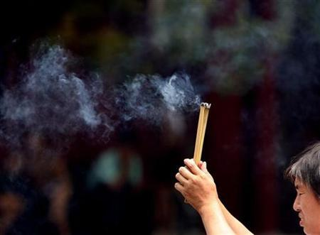 A man prays with incense sticks at the more than 300-year-old Yong He Gong, also known as the Tibetan Lama Temple, in Beijing July 7, 2008. REUTERS/David Gray