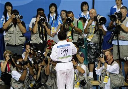 Judo gold medallist in women's -63kg category Ayumi Tanimoto of Japan poses for photographers after the medal ceremony at the Beijing 2008 Olympic Games, August 12, 2008. REUTERS/Issei Kato