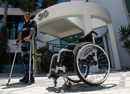 Radi Kaiof stands near a wheelchair using an electronic exoskeleton at a development center in the northern city of Haifa August 18, 2008. REUTERS/Baz Ratner