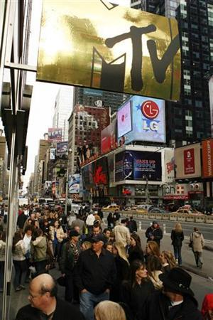 Pedestrians walk past a sign with the MTV logo on it below the MTV studios in Times Square New York December 12, 2007. REUTERS/Lucas Jackson