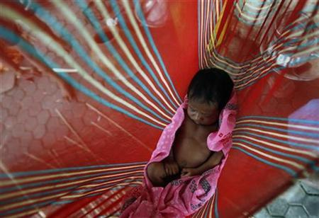 A child belonging to a family of pavement dwellers, sleeps in a cradle at a street in Mumbai July 8, 2008. REUTERS/Arko Datta