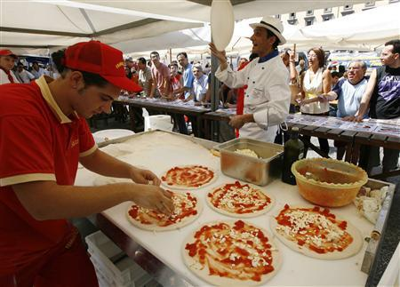 Chefs prepare free pizza while staging a protest to demand stricter price controls on the rising cost of pizza in Naples August 27, 2008. REUTERS/Ciro De Luca/Agnfoto