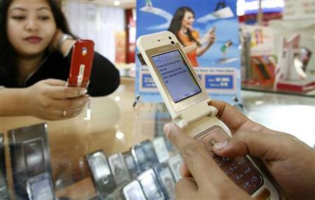 A customer sends a text message from her phone in a mobile phone shop in Jakarta June 18, 2008. REUTERS/Crack Palinggi