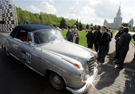 A Mercedes classic car drives past spectators during a car show in front of Moscow's State University building May 20, 2006. REUTERS/Alexander Natruskin