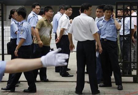 Policemen keep watch outside Shanghai Zhabei's district police station in Shanghai July 1, 2008. REUTERS/Stringer