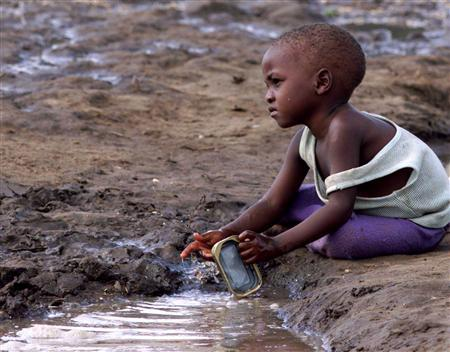 A young child plays in a stagnant pool of water in Mozambique in a file photo. Major inequalities in health and life expectancy persist worldwide, according to an independent World Health Organization commission which on Thursday called for all countries to offer universal health care. REUTERS/File