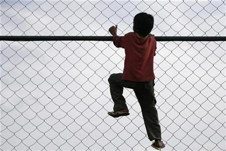 A boy climbs a fence in Kathmandu July 26, 2008. REUTERS/Shruti Shrestha