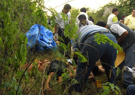 Police investigators work at a crime scene where eleven beheaded bodies were dumped close to a graveyard outside the village of Chichi Suarez in Yucatan Peninsula, Mexico on August 28, 2008. The beheadings of twelve people in southern Mexico were probably the work of the powerful Gulf cartel based across the border from Texas, a state governor said on Friday. REUTERS/Argely Salazar