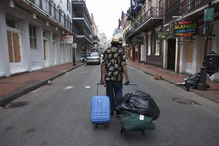 A man hauls bags down Bourbon Street in the French Quarter of New Orleans, Louisiana, ahead of Hurricane Gustav's arrival, August 31, 2008. Hurricane Gustav churned toward the Louisiana coast through the oil-rich Gulf of Mexico on Sunday with strength that could rival 2005's Hurricane Katrina, prompting low-lying New Orleans to begin evacuation. REUTERS/Lee Celano