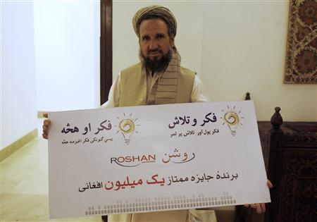 Faizulhaq Moshkani holds a one million Afghani ($20,000) prize after coming first in a reality TV show in Kabul August 10, 2008. A reality TV show broadcast in Afghanistan has encouraged Afghans to start their own enterprises, stirring entrepreneurial spirits in a country that has been ravaged by three decades of war. Picture taken August 10, 2008. REUTERS/Jonathon Burch