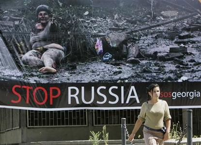 A girl walks past a banner in Tbilisi, August 31, 2008. REUTERS/David Mdzinarishvili