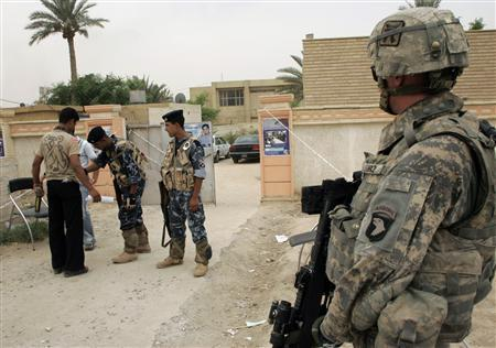 A U.S. soldier looks at Iraqi soldiers checking a resident in Mahmudiya, south of Baghdad, August 25, 2008. REUTERS/Ibrahim Sultan