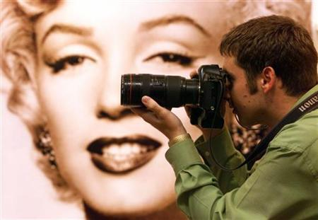 A photographer takes pictures at an exhibition of Marilyn Monroe property at an auction house in a file photo. An amateur film of Marilyn Monroe on the set of ''Some Like It Hot'' has surfaced in Australia almost 50 years after it was shot and is being put up for auction. REUTERS/Paul Hackett
