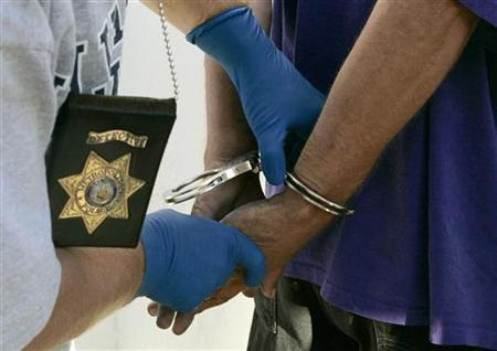 A plainclothes detective with the Las Vegas Metropolitan Police Department handcuffs a man on the Las Vegas Strip, August 8, 2007. REUTERS/Steve Marcus