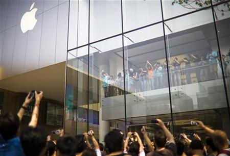 Employees wave to people at the first direct-sale Apple Store in China at Sanlitun district of Beijing July 19, 2008. REUTERS/Stringer