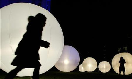 Children play near illuminated balloons during a company's Christmas party in the northern German town of Hamburg December 7, 2004. REUTERS/Christian Charisius