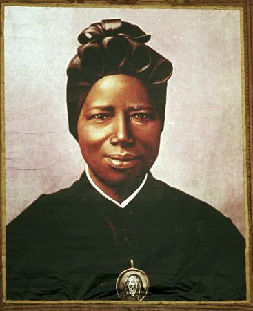 A tapestry portrait of Mother Josephine Bakhita, a Sudanese former slave and nun who died in 1947, hangs during her cannonisation at the Vatican October 1, 2000. REUTERS/Osservatore Romano