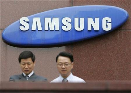 Employees of Samsung Group walk in front of the company's logo at its headquarters in Seoul April 22, 2008. Samsung Electronics Co Ltd said on Friday it was considering ''various opportunities'' regarding SanDisk, in response to reports it was interested in bidding for the U.S. flash memory maker. REUTERS/Jo Yong-Hak
