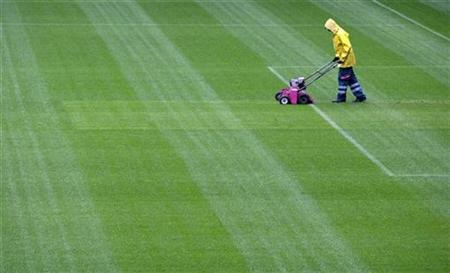 A worker cuts the new turf at the Stade de Suisse soccer stadium in Bern May 26, 2008. Exhaust-spewing lawn mowers and speed boats will get a green make-over under tough new rules from the U.S. Environmental Protection Agency designed to reduce smog and save millions of gallons of gasoline. REUTERS/Ruben Sprich