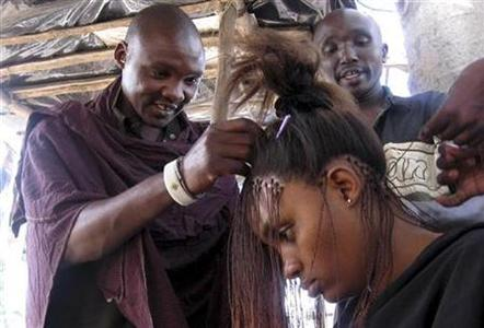 Kenyan Maasai warriors braid their client's hair in the Kenyan coastal city of Mombasa, July 26, 2008. REUTERS/Guled Mohamed