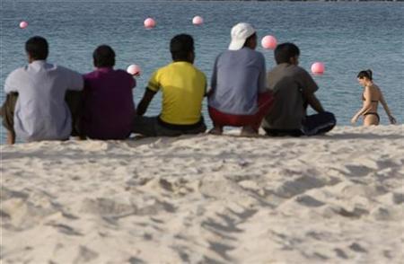 Men sitting on the beach watch beach-goers in Dubai December 2, 2007. REUTERS/Steve Crisp
