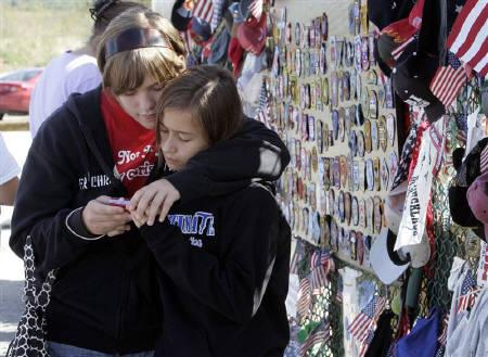 Marisa Gratton, 14, (L) and her sister Tara, 11, (R) of Monroeville, Pennsylvania look at photos they had just taken at the Flight 93 Temporary Memorial outside Shanksville, Pennsylvania, September 10, 2008. REUTERS/ Jason Cohn