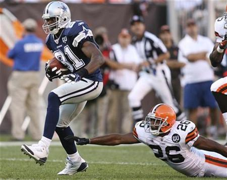 Dallas Cowboys Terrell Owens runs from the grasp of Cleveland Browns defender Sean Jones during the third quarter of their game in Cleveland, September 7, 2008. REUTERS/Aaron Josefczyk