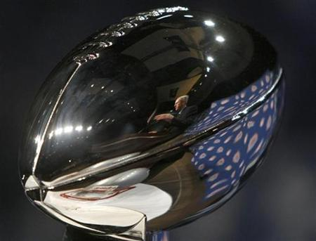 New York Giants head coach Tom Coughlin is reflected in the Vince Lombardi Trophy as he answers questions at a news conference in Phoenix, February 1, 2008. REUTERS/Rick Wilking