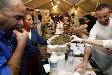 "<p>Volunteers serve meals to the needy at the non-profit ""Une Chorba Pour Tous"" (soup for everyone) soup kitchen in a tent outside a public housing project in Paris in this September 8, 2008 file photo. REUTERS/Benoit Tessier/Files</p>"