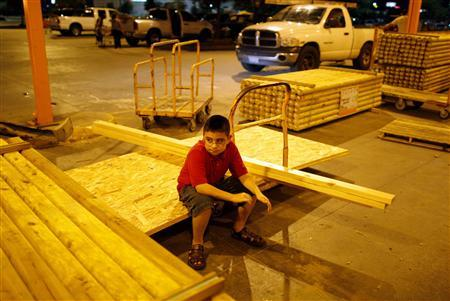 A boy waits for his parents as they buy plywood for protection against Hurricane Ike in Houston, Texas September 11, 2008. REUTERS/Carlos Barria