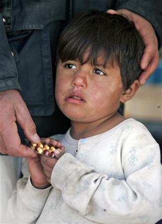 A boy holds a pack of medicine distributed by the Red Crescent to displaced families at a refugee camp in Yusufiya, 9 miles south of Baghdad, December 3, 2007. REUTERS/Thaier al-Sudani