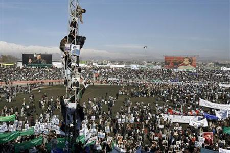 People climb up a tower during a gathering in Kabul's stadium February 23, 2007. REUTERS/Ahmad Masood