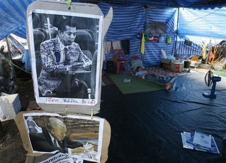 An anti-government protester rests next to old and current images of former Thai Prime Minister Samak Sundaravej during a demonstration outside the Government House in Bangkok September 13, 2008. REUTERS/Chaiwat Subprasom