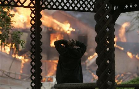Eric Archuleta watches his neighbors house burn after Hurricane Ike hit Galveston, Texas September 13, 2008. REUTERS/Jessica Rinaldi