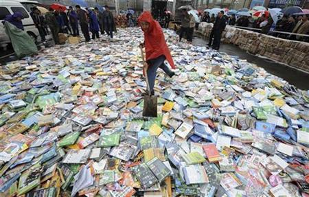 A local official shovels pirated DVDs before destroying them during a campaign in Taiyuan, Shanxi province, April 20, 2008. REUTERS/Stringer