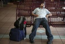<p>A man sleeps at a Greyhound bus station in Mobile, Alabama, May 11, 2007. REUTERS/Carlos Barria</p>