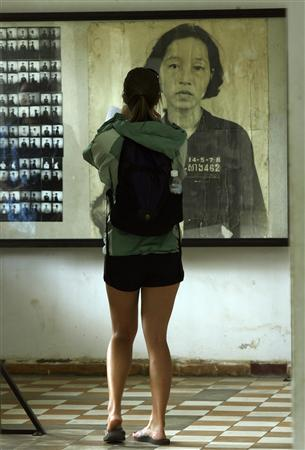 A tourist takes a picture of portraits of Khmer Rouge victims on display at the Tuol Sleng genocide museum, which served as the notorious ''S-21'' interrogation and torture centre during the regime, in Phnom Penh September 16, 2008. REUTERS/Chor Sokunthea