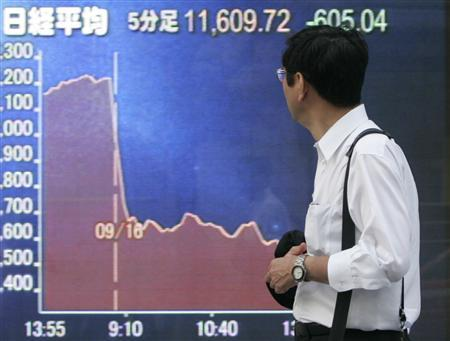 A man looks at an electronic board displaying a graph of Japan's Nikkei share average in Tokyo September 16, 2008. REUTERS/Yuriko Nakao