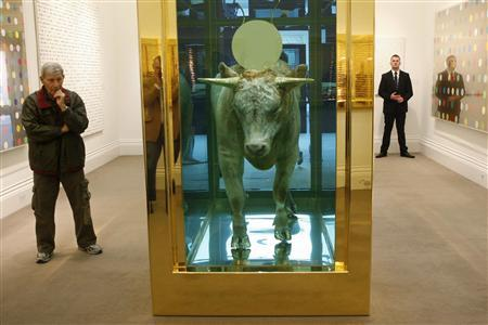 A visitor looks at ''The Golden Calf'' by artist Damien Hirst at Sotheby's in London in this September 8, 2008 file photograph. Hirst's bull in a tank of formaldehyde with its head crowned by a gold disc sold for 10.35 million pounds ($18.6 million) on September 15, 2008, a record a auction for one of the contemporary art world's stars, Sotheby's said. REUTERS/Suzanne Plunkett/Files