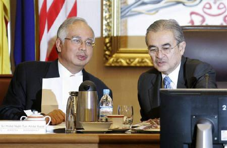 Malaysian Prime Minister Abdullah Ahmad Badawi (R) talks to his deputy Najib Razak before the United Malays National Organisation (UMNO) party supreme council meeting at its headquarters in Kuala Lumpur July 10, 2008, file photo. REUTERS/Zainal Abd Halim