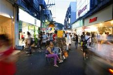 <p>A woman sits beside her stall at the Shilin night market in Taipei July 15, 2008. REUTERS/Nicky Loh</p>