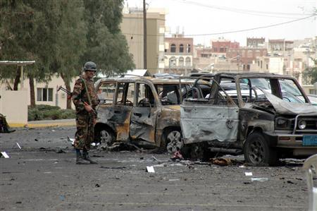 A Yemeni soldier stands next to two burnt cars outside the U.S. embassy in Sanaa September 18, 2008. Yemeni authorities have arrested 30 people suspected of belonging to al Qaeda following an attack on the heavily fortified U.S. embassy in Sanaa, a security source said on Thursday. Two suicide car bombs set off a series of explosions outside the embassy compound on Wednesday, killing 16 people including six attackers. The dead were all Yemeni apart from an Indian woman who was walking past when the attack happened. REUTERS/ Stringer